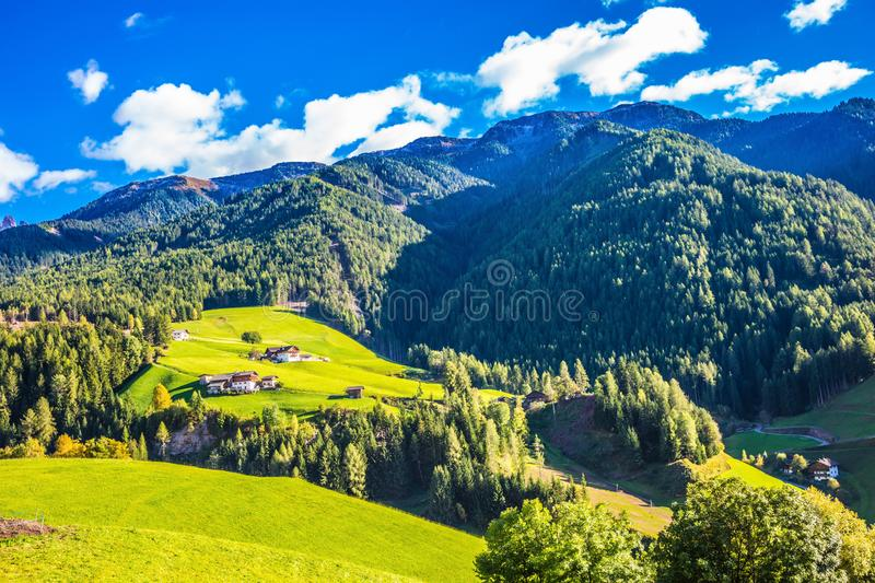 Rural pastoral in the Val de Funes. Rural pastoral in the Dolomites. Warm autumn day. Charming chalet on a green grassy slope of the mountain. The concept of royalty free stock image