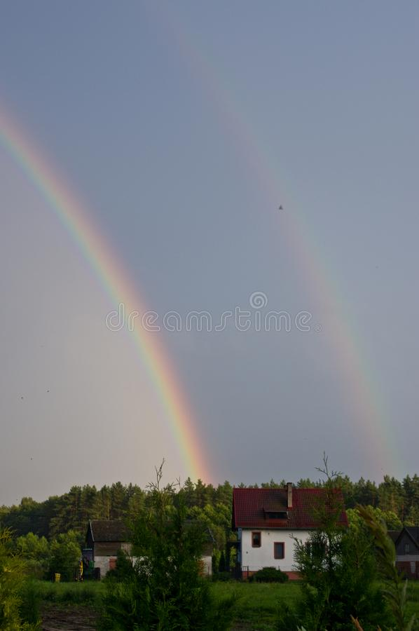 Rural Poland, Ilawa region, rainbow over village of Sapy royalty free stock image