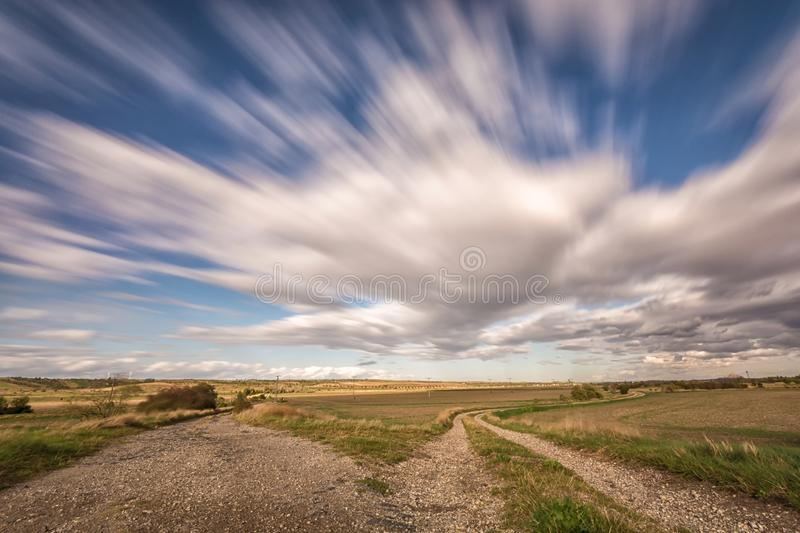 Rural region with two dirt roads and fast passing clouds royalty free stock photography