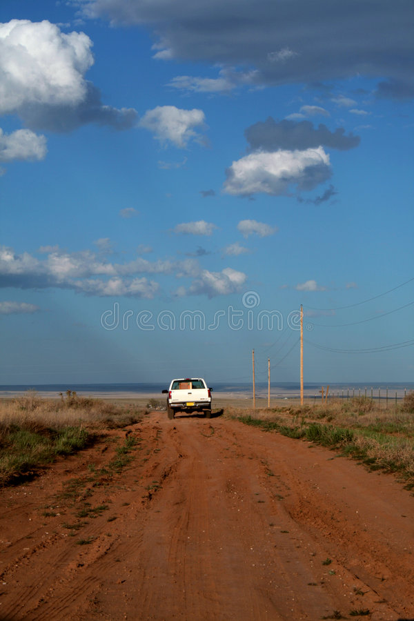 Rural Road. A white pickup truck drives down a dusty, dirt rural road with some homes barely visible in the distance royalty free stock images