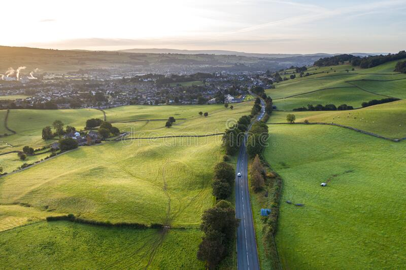Rural Road Across Farming Fields at Sunrise. Aerial shoot over countryside road along rolling farming fields near Kendal in Lake District National Park, United stock images