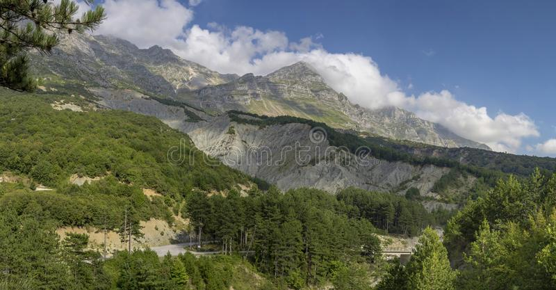 Rural road in the mountains region Tzoumerka, Epirus, Greece. View of a rural, narrow road and mountains on a sunny, summer day region Tzoumerka, Epirus, Greece royalty free stock photography