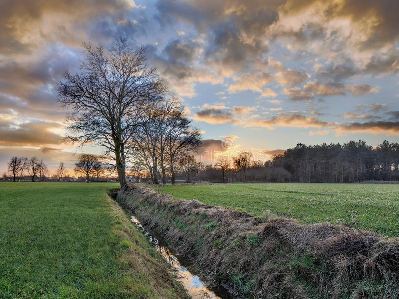 Rural scenery, field with trees near a ditch and colorful sunset with dramatic clouds, Weelde, Belgium stock images