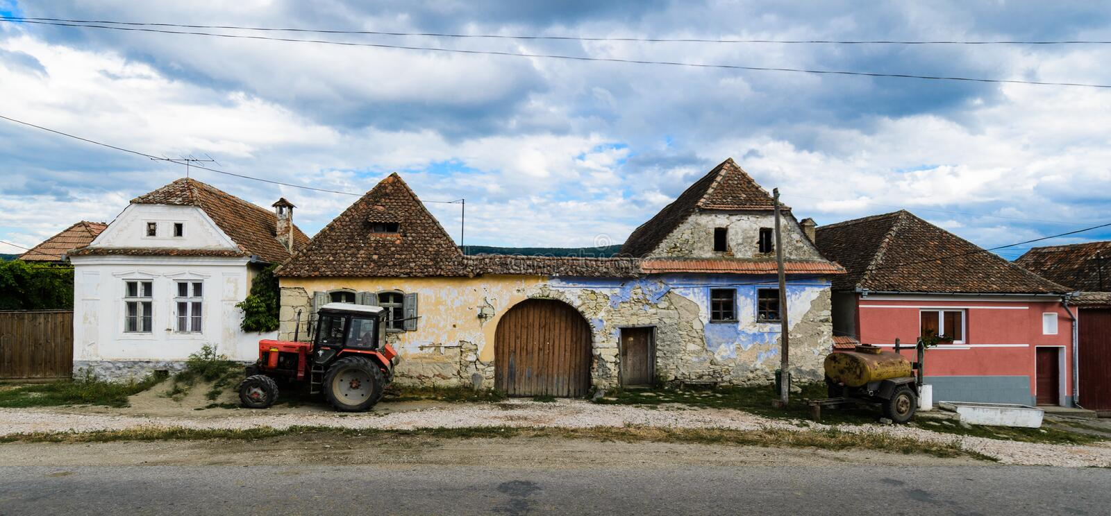 Rural semidetached house with agricultural machinery stock images