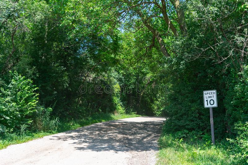Rural Shaded Dirt Road in a Forest with Green Trees and Speed Limit Sign. An empty rural shaded dirt road in a forest with green trees in the Chicago suburb of royalty free stock photography