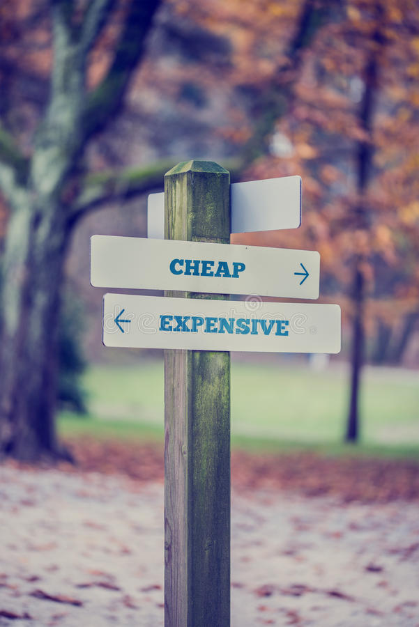 Rural signboard with two signs saying - Cheap - Expensive royalty free stock image