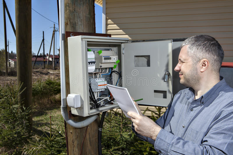 Rural Technician Taking Reading Of Electric Meter in the country royalty free stock images