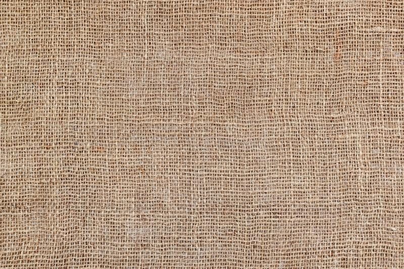 Rural texture of sackcloth. Background of very coarse, rough fabric woven made of flax, jute or hemp. Burlap bag material. Design royalty free stock photo