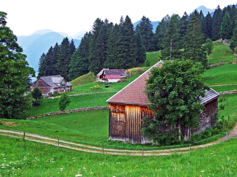 Rural traditional architecture and livestock farms on the slopes of Alpstein mountain range and in the river Thur valley. Canton of St. Gallen, Switzerland royalty free stock photography