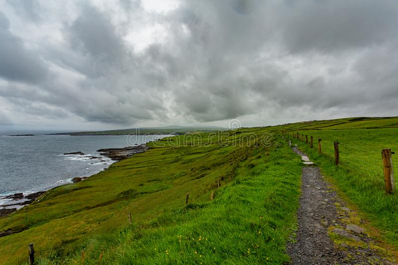 Rural trail between the Irish countryside of the coastal route walk from Doolin to the Cliffs of Moher. Geosites and geopark, Wild Atlantic Way, cloudy day in stock photo