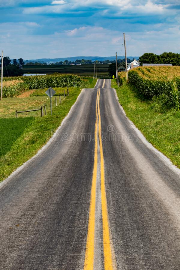 Rural Two-lane Country Road. Paradise, PA, USA - August 8, 2015: A rural, two-lane country road in farmland during the summer in Lancaster County, Pennsylvania stock images