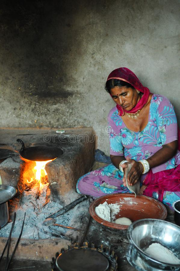 Young woman preparing wood to light fire for cooking in