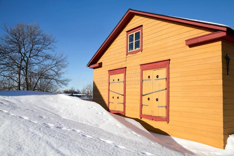 Rural yellow wooden house in winter season stock photos