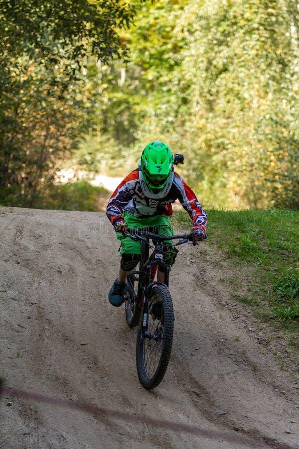 Rusa för bergcyklist som är sluttande på ett mountainbikespår i träna fotografering för bildbyråer