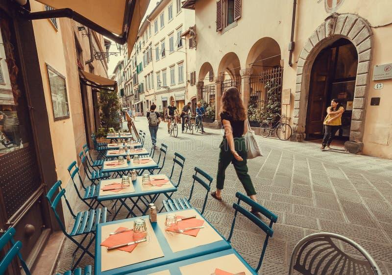 Rusa går folket förbi utomhus- restaurang med tabeller och uppsättningar i gammal stad royaltyfria bilder