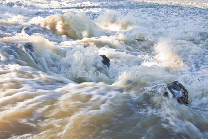 Rusa vatten av en svullen flod under den regniga säsongen arkivfoton