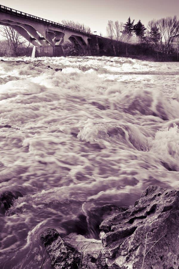 Rusa vatten av en svullen flod under den regniga säsongen med a fotografering för bildbyråer