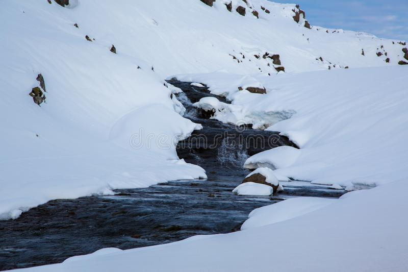 Ruscello nella neve negli altopiani dell'Islanda fotografia stock