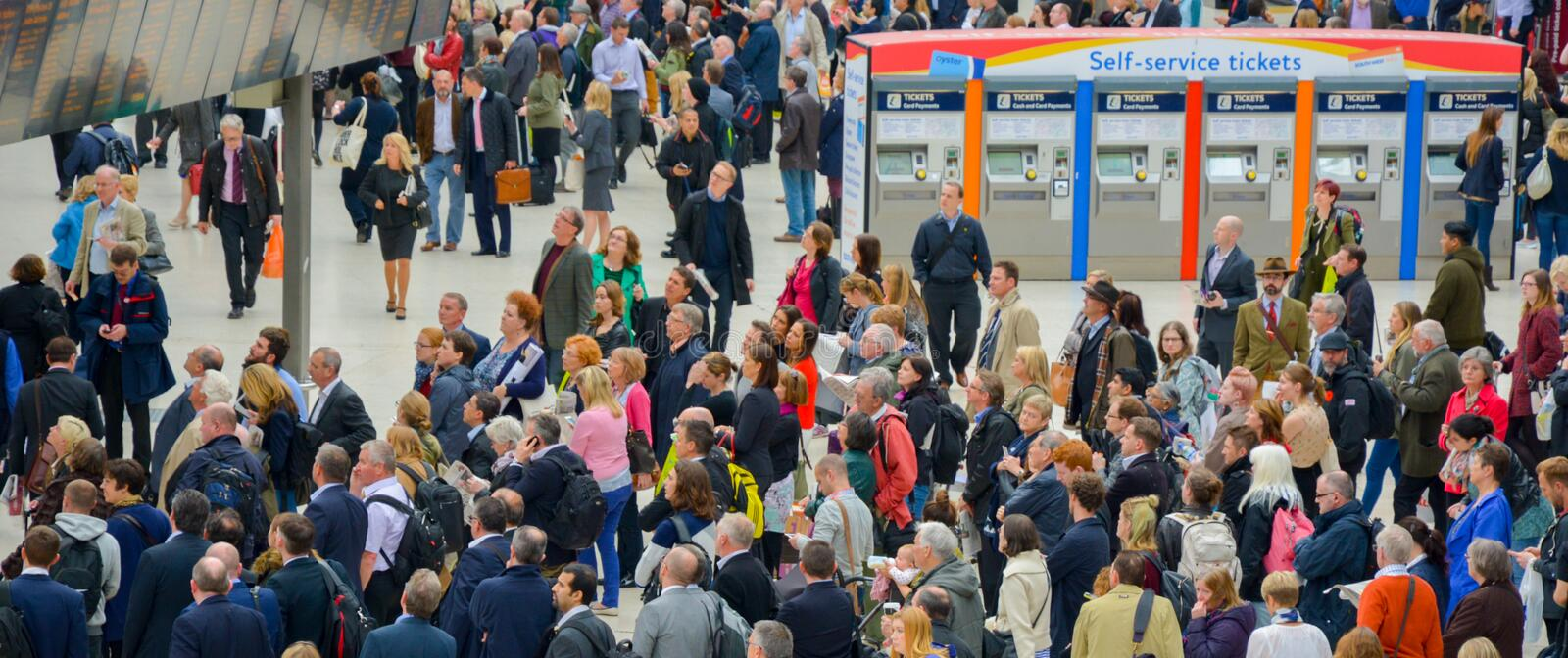 Rush hour crowds at Waterloo Train Station London. A picture of commuters at rush hour on Waterloo station checking the train timetables stock image