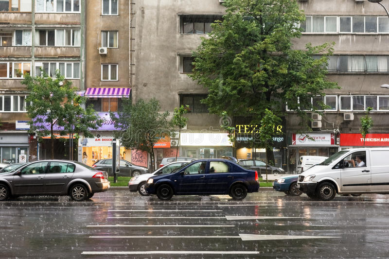 Rush Hour Traffic During Summer Storm. BUCHAREST, ROMANIA - JUNE 20, 2014: Rush Hour Traffic Downtown Bucharest On Magheru Avenue During Powerful Summer Storm stock photo