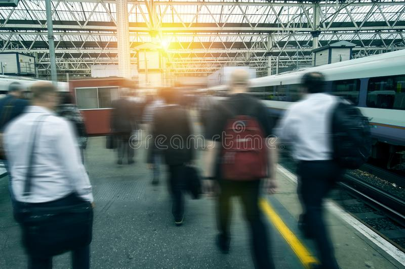 Rush hour at the train station. People commuter walking. Blurred city workers and business people going to work in rush in London.  royalty free stock photography