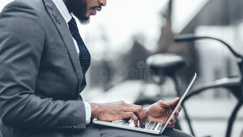 Rush job. Businessman using laptop, sitting on bench in city. Closeup, crop royalty free stock photos