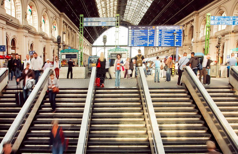 Rushing people inside the structure of Keleti railway station with trains on platform royalty free stock photography