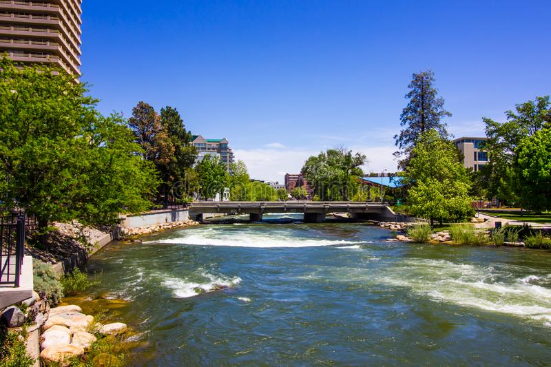 Rushing River Under Bridge In Downtown Area. Rushing River Waters Flowing Under Traffic Bridge In Downtown Area stock photos