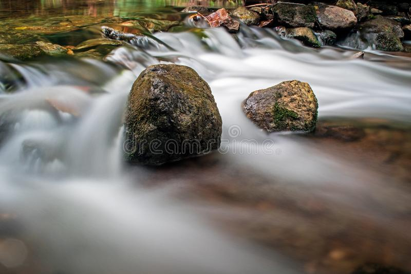 Rushing Water Blurred On The Boyne River. A moss covered rock sits solid in the fast moving waters of the Boyne River, just upstream from Hoggs Falls. The royalty free stock photo