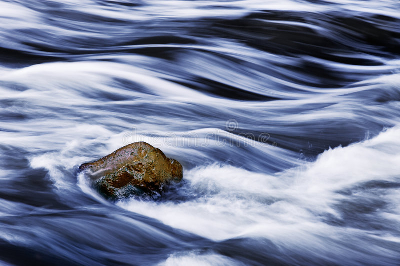 Rushing Water And Rock. Water rushing by a rock in a river forming a smooth, abstract, painted appearing pattern