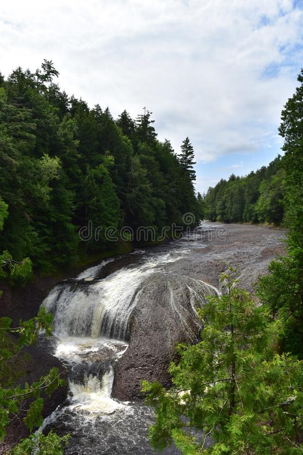 Rushing waterfall in a wilderness area on a hazy summer day. Potawatomi Falls on the Black River in the Porcupine Mountains area of upper Michigan royalty free stock photo