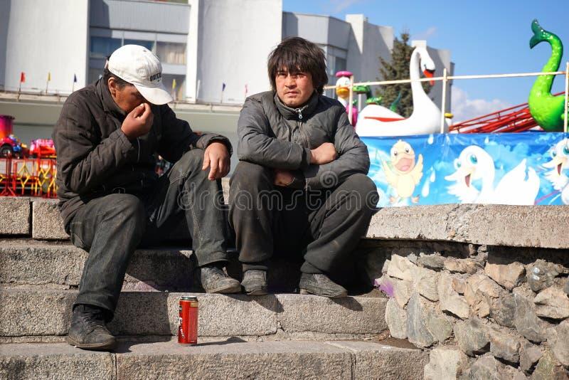 Rusia, ciudad de Magnitogorsk, - abril, 18, 2015 Dos vagabundo se está sentando en los pasos cerca del parque de los niños fotos de archivo libres de regalías