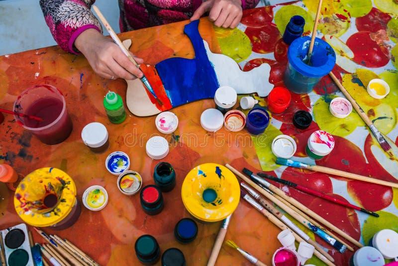 Rusia, ciudad de Yaroslavl - 4 de mayo de 2019: El niño sostiene un cepillo Colorear a un tablero de madera Estudio creativo o le fotos de archivo