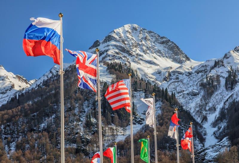 Rusia, Gran Bretaña, los E.E.U.U. y otras banderas nacionales agitan en fondo del pico de montaña foto de archivo libre de regalías