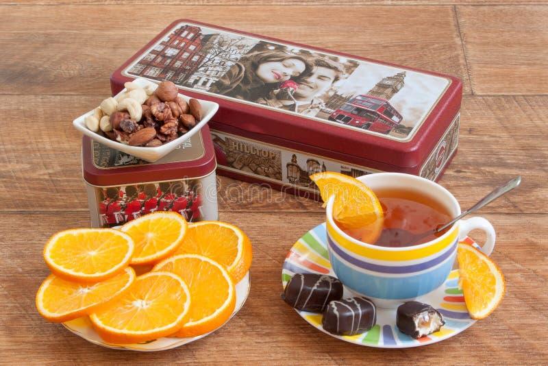 Rusia, Izhevsk - 15 de mayo de 2017: Cumbre del juego de té Té verde negro y chino de Ceilán Rebanadas de naranja y de dulces fre foto de archivo libre de regalías