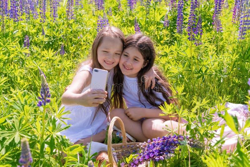Rusia, Kazán - 7 de junio de 2019 dos bebés hacen el selfie en un teléfono entre las flores en un campo en un día soleado El conc foto de archivo libre de regalías