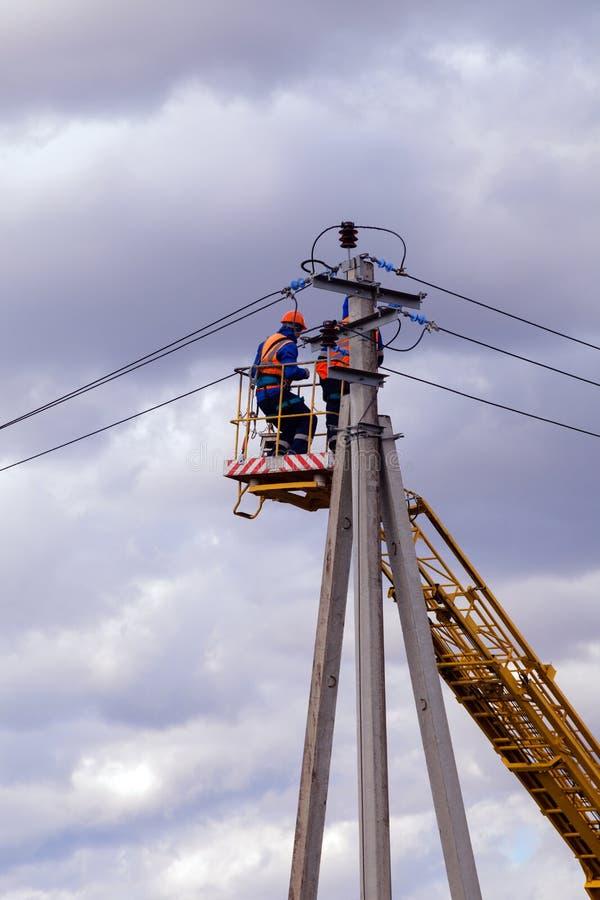 Rusia, Kemerovo, combina de electricistas en cascos y uniforma r foto de archivo libre de regalías