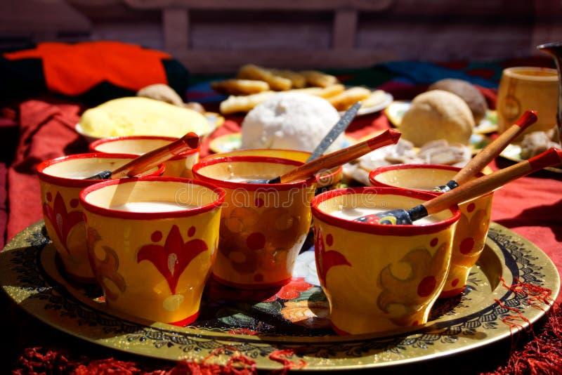 Rusia, Magnitogorsk, - junio, 15, 2019 Koumiss - la leche de la yegua en tazas y platos de madera nacionales tradicionales de bas fotografía de archivo