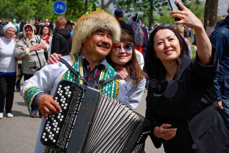 Rusia, Magnitogorsk, - junio, 15, 2019 Las muchachas toman un selfie con un acordeón en traje popular durante Sabantuy - el nacio imagen de archivo libre de regalías