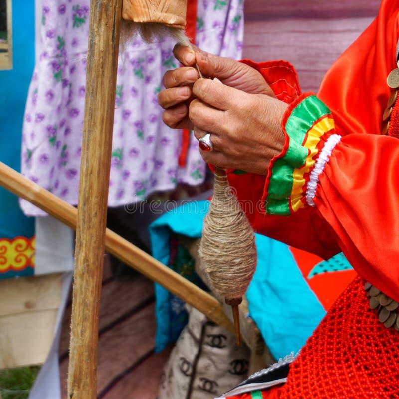 Rusia, Magnitogorsk, - junio, 15, 2019 Manos que hacen girar a una mujer con un eje durante el día de fiesta Sabantuy Vestido nac foto de archivo