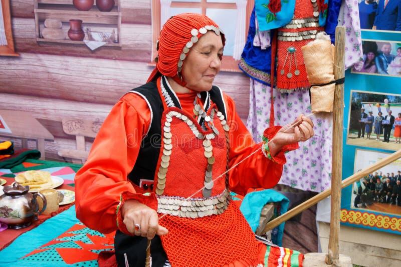 Rusia, Magnitogorsk, - junio, 15, 2019 Una mujer mayor demuestra el trabajo de una rueda de hilado manual durante el Sabantui fotografía de archivo