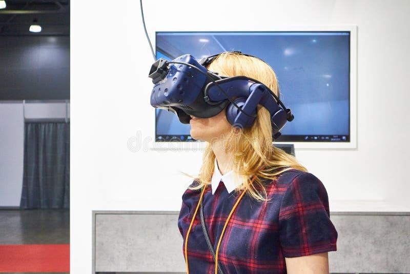 RUSIA, MOSCÚ - ABRIL, 04, 2019 miradas de la muchacha de A en un casco de la realidad virtual fotos de archivo