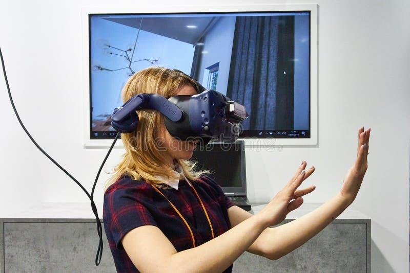 RUSIA, MOSCÚ - ABRIL, 04, muchacha rubia joven 2019 en auriculares aumentadas de la realidad imágenes de archivo libres de regalías