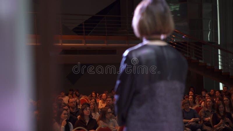 RUSIA, MOSCÚ - 13 DE ABRIL DE 2019: La mujer da conferencia en etapa con la audiencia Arte La mujer acertada hace discurso encend imagen de archivo