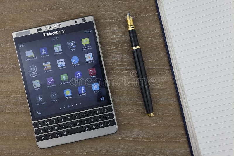 RUSIA, MOSCÚ, febrero de 2017 visión desde el top en el smartphone, la pluma y el cuaderno de Blackberry poniendo en la tabla fotos de archivo