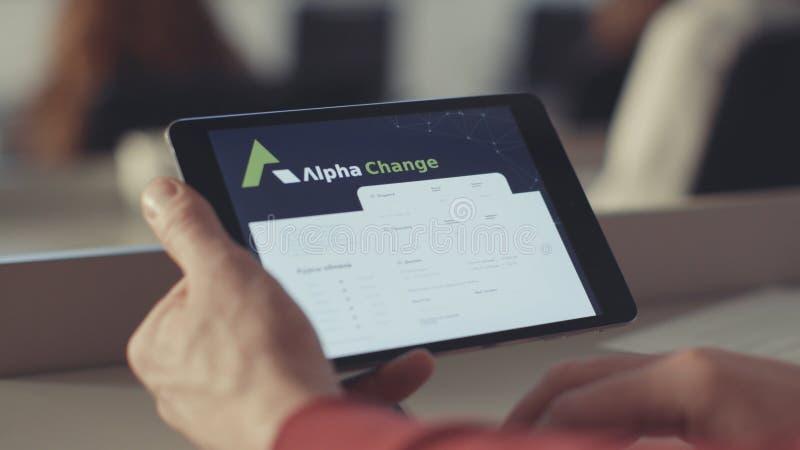 Rusia, Moscú - mayo de 2018: el hombre comprueba la cuenta en la tableta existencias Comprobación del equilibrio del bitcoin en l foto de archivo libre de regalías