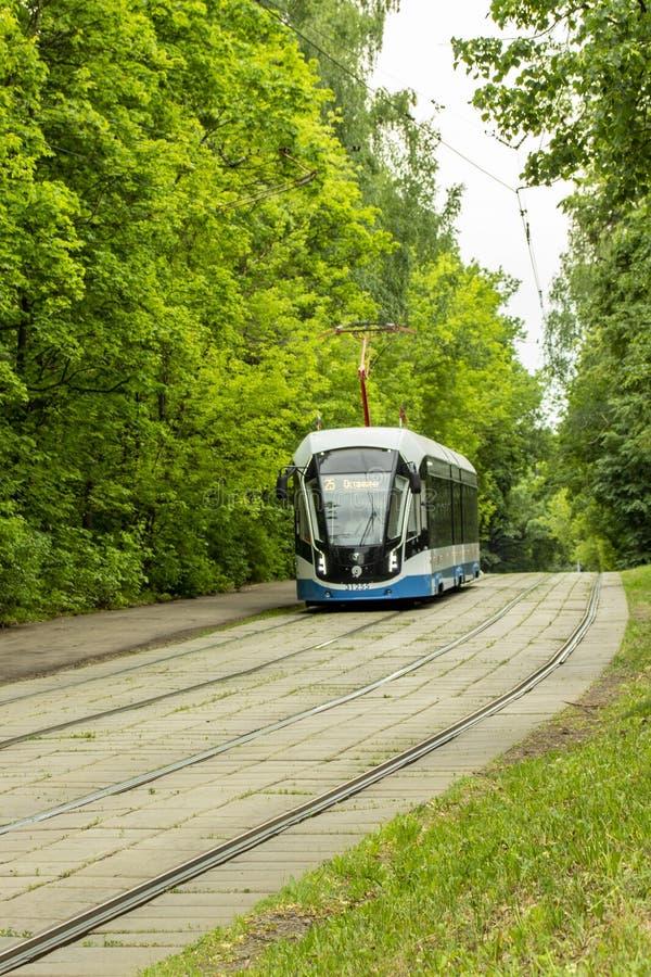 12-06-2019, Rusia, Moscú Movimientos azules de la tranvía de Moscú en los carriles contra la perspectiva del follaje verde del ve imagen de archivo