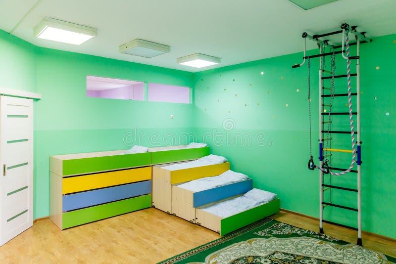 Rusia, Moscú, 02 01 2019: Resto en una guardería pública Muchas camas en el dormitorio Sitio vacío con las paredes verdes imagen de archivo