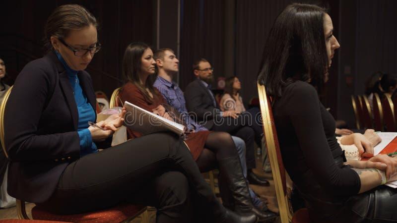 RUSIA, MOSC? - 13 DE ABRIL DE 2019: La audiencia de las mujeres que escucha los entrenamientos y las conferencias de la informaci fotos de archivo