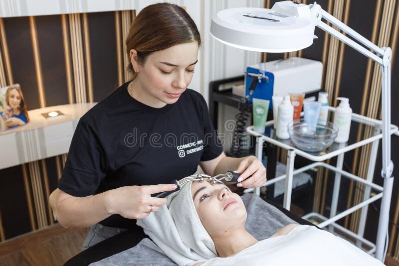 Rusia, Mosc?, el 18 de mayo de 2019 Un paciente recibe un masaje facial eléctrico del cosmetologist en clínica estética foto de archivo